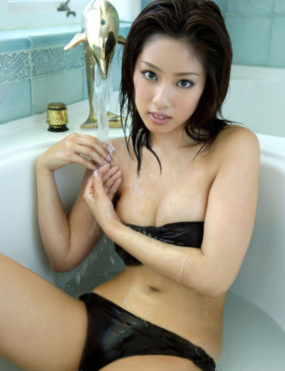 An Asian masseuse sat in a bath in her black bikini