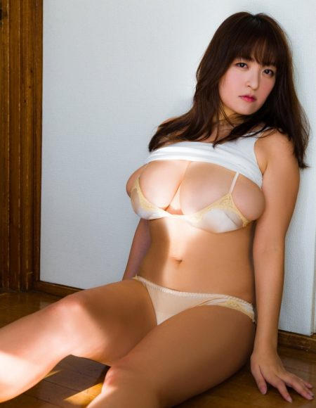 A super busty Asian masseuse sat on a wooden floor with her top pulled up
